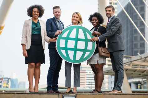five people standing while holding green globe art